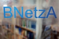 """Auf einer Glas-Tür in der Bundesnetzagentur steht die Abkürzung der Behörde: """"BNetzA"""""""