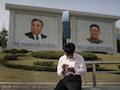 Ein Nordkoreaner sitzt in Pjöngjang vor den Gemälden der verstorbenen nordkoreanischen Diktatoren Kim Il Sung (l) und Kim Jong-il (r) und nutzt sein Smartphone.