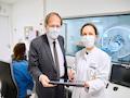 Prof. Wolfgang Holzgreve (links), Ärztlicher Direktor und Vorstandsvorsitzender am UKB und Prof. Ulrike Attenberger, Direktorin der Klinik für Diagnostische und Interventionelle Radiologie besprechen die Bilder einer MRT-Untersuchung auf dem Tablet.
